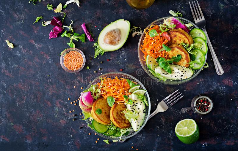 Vegan buddha bowl dinner food table. Healthy food. Healthy vegan lunch bowl. Fritter with lentils and radish, avocado, carrot sala. D. Flat lay. Top view royalty free stock photo