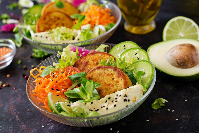 Vegan buddha bowl dinner food table. Healthy vegan lunch bowl. Fritter with lentils and radish, avocado, carrot salad. Vegan buddha bowl dinner food table royalty free stock image