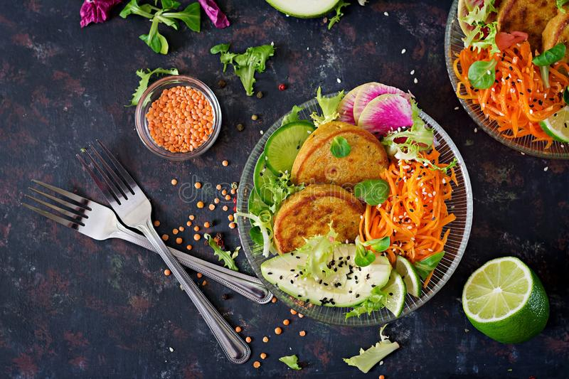 Vegan buddha bowl dinner food table. Healthy food. Healthy vegan lunch bowl. Fritter with lentils and radish, avocado, carrot sala stock image