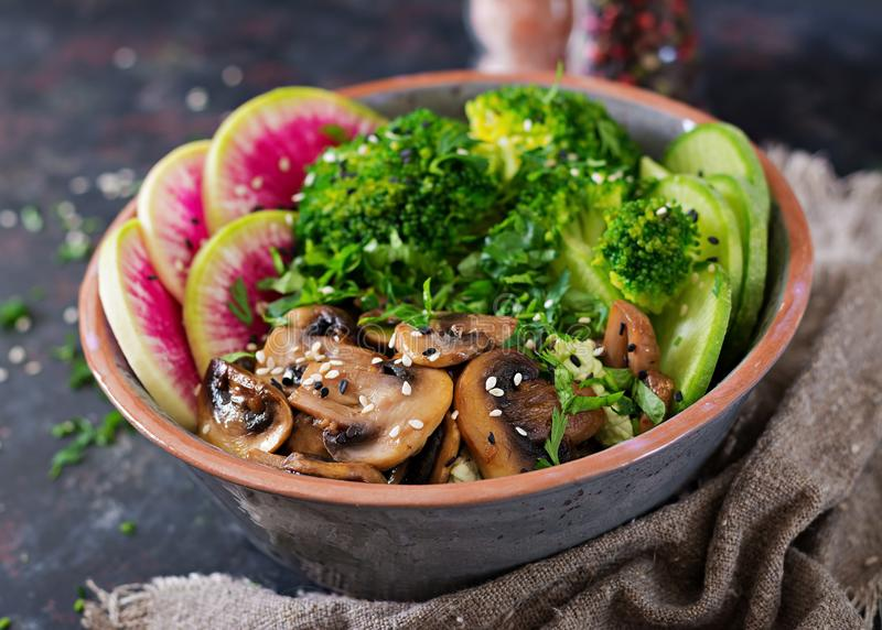 Vegan buddha bowl dinner food table. Healthy vegan lunch bowl. Grilled mushrooms, broccoli, radish salad. Vegan buddha bowl dinner food table. Healthy food stock photography