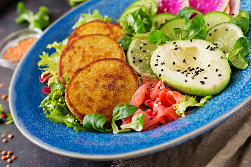Vegan buddha bowl dinner food table. Healthy vegan lunch bowl. Fritter with lentils and radish, avocado salad royalty free stock photography