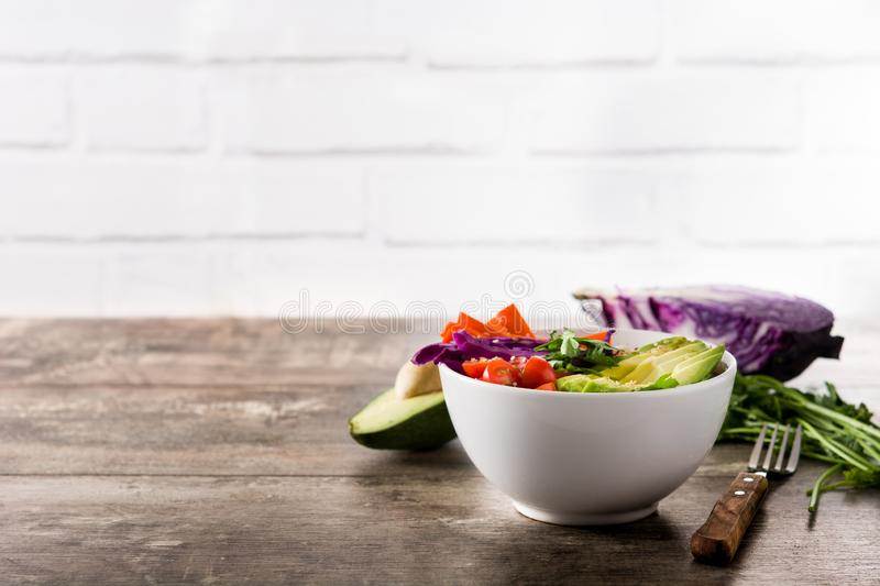 Vegan Buddha bowl with fresh raw vegetables and quinoa on wood royalty free stock image