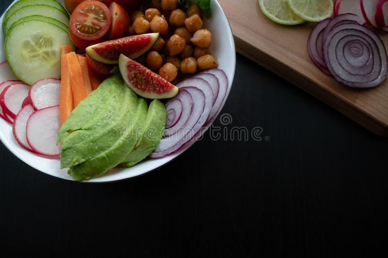 Close up view of Buddha bowl with avocado, figs, chickpeas. Copy space. Vegan Buddha bowl made wit organic vegetables such as avocado, radish, cucumber, carrot royalty free stock images