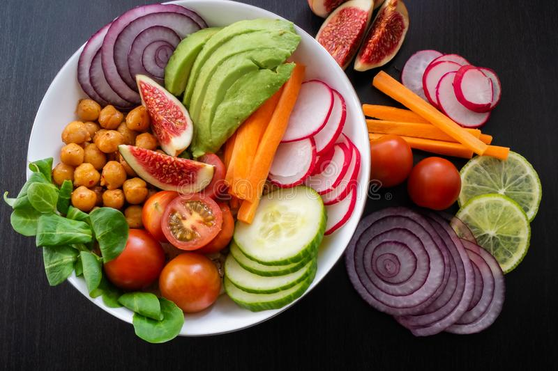 Vegan Buddha bowl with organic and fresh ingredients. Top view. Vegan Buddha bowl made wit organic vegetables such as avocado, radish, cucumber, carrot stock photos