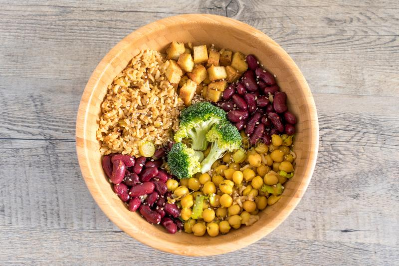 Vegan buddha bowl with stir fry tofu, brown rice, broccoli, red kidney beans, cooked chickpeas, seeds and vegetables. Flat lay. stock photography