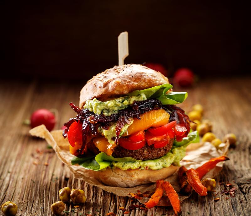 Vegan burger, carrot burger, homemade burger with carrot cutlet, grilled bell pepper, cherry tomatoes, red onion chutney, lettuce, stock photo