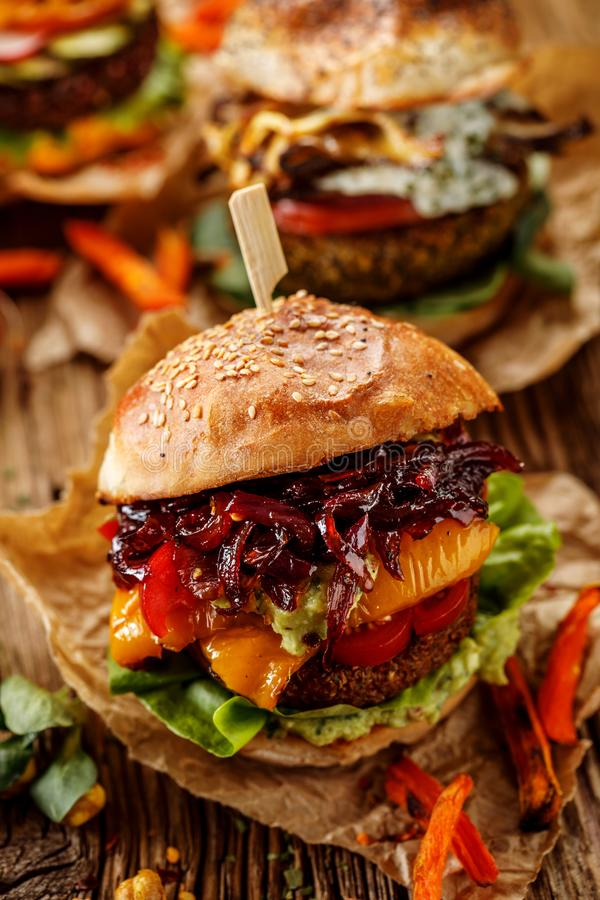 Vegan burger, carrot burger, homemade burger with carrot cutlet, grilled bell pepper, cherry tomatoes, red onion chutney, lettuce, royalty free stock image