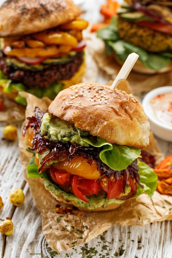 Vegan burger, carrot burger, homemade burger with carrot cutlet, grilled bell pepper, cherry tomatoes, red onion chutney, lettuce, royalty free stock photography
