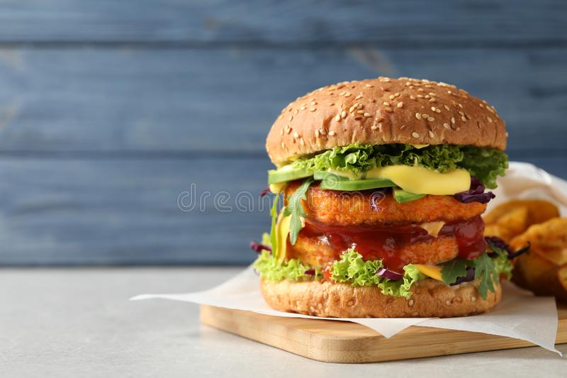 Vegan burger with carrot patties served on table against color background. Space for text royalty free stock photos