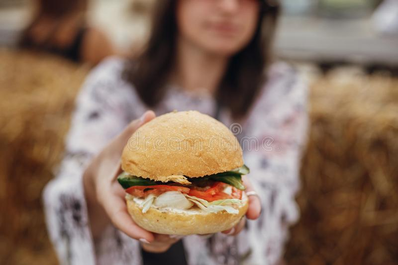 Vegan burger closeup in boho girl hands. Stylish hipster girl in sunglasses eating delicious vegan burger at street food festival royalty free stock photo