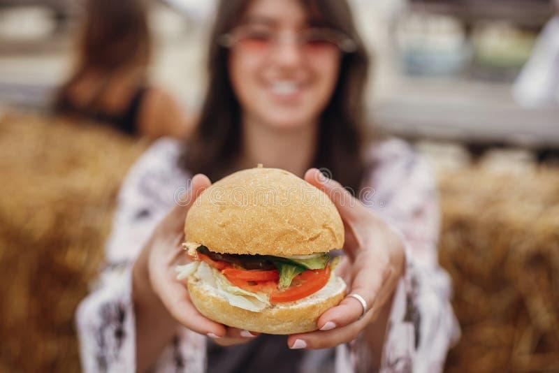 Vegan burger closeup in boho girl hands. Stylish hipster girl in sunglasses eating delicious vegan burger at street food festival. Happy boho woman tasting and royalty free stock image