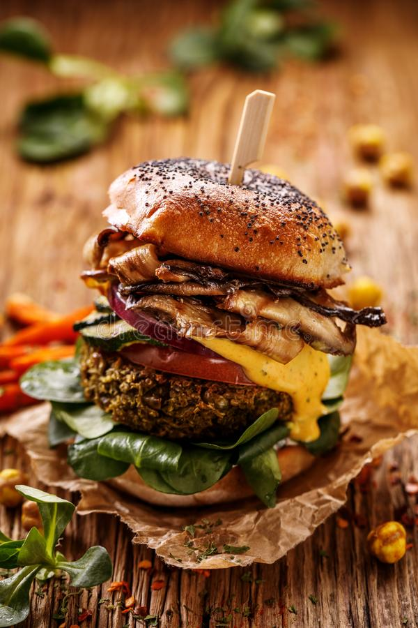 Vegan burger, green peas burger, homemade burger with green peas cutlet, grilled mushrooms, tomato, red onion, lamb`s lettuce, and royalty free stock photos