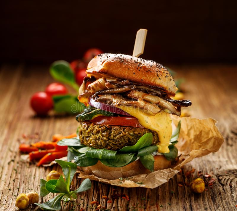 Vegan burger, green peas burger, homemade burger with green peas cutlet, grilled mushrooms, tomato, red onion, lamb`s lettuce, and stock image