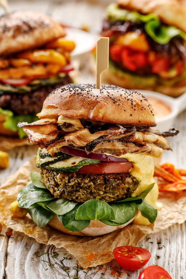 Vegan burger, green peas burger, homemade burger with green peas cutlet, grilled mushrooms, zucchini, tomato, red onion, lamb`s l stock images