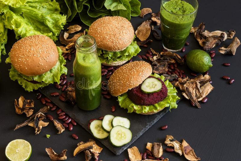 Vegan burgers with beet cutlet and green smoothies on black background. Healthy vegan food. Detox diet. stock photography