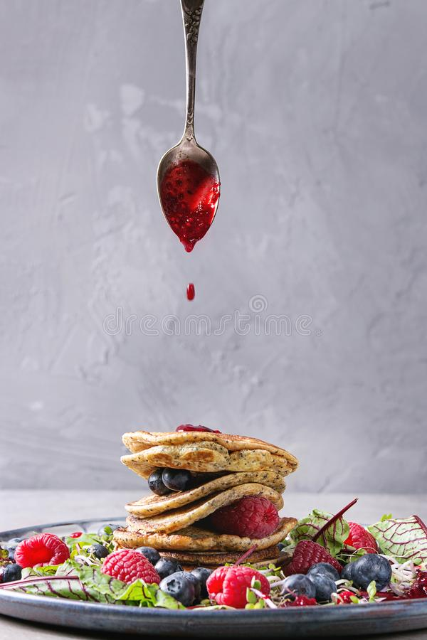 Vegan pancakes with greens. Vegan chickpea pancakes served in plate with green salad young beetroot leaves, sprouts, berries, berry sauce flowing from spoon over royalty free stock images