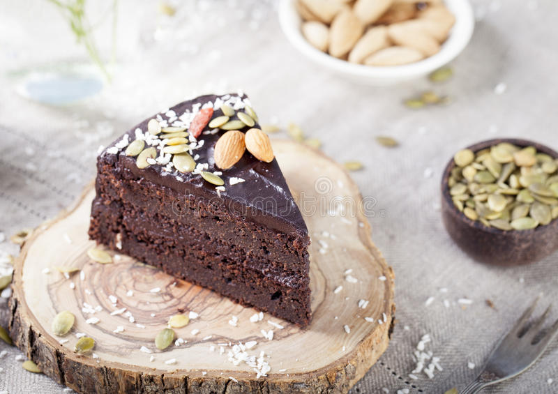 Vegan chocolate beet cake with avocado frosting, decorated nuts, seeds. Vegan chocolate beet cake with avocado frosting, decorated with nuts and seeds royalty free stock photography