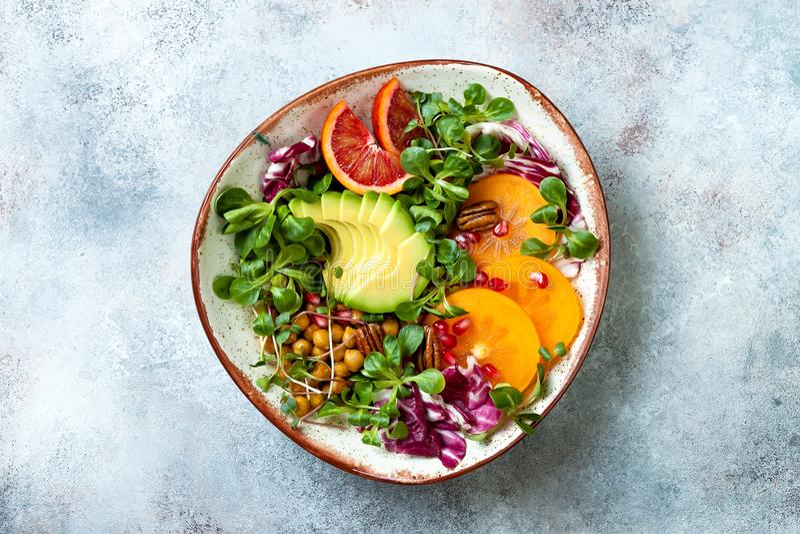 Vegan, cuvette de Bouddha de detox avec les pois chiches rôtis par safran des indes, verts, avocat, kaki, orange sanguine, écrous photo stock