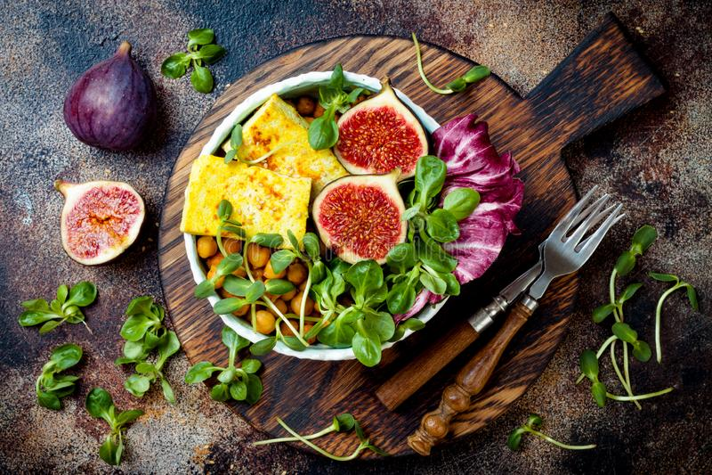 Vegan, detox Buddha bowl recipe with turmeric roasted tofu, figs, chickpeas and greens. Top view royalty free stock images