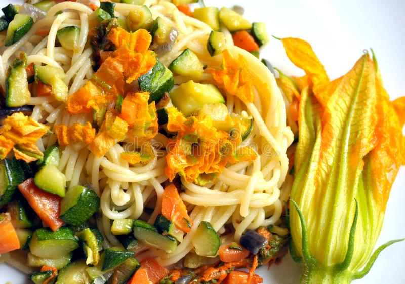 Vegan dish : squash blossom pasta. Squash blossom pasta . Vegetarian meal with zucchini , carrot , violet onion and squash blossoms on a white plate. cooking royalty free stock photography