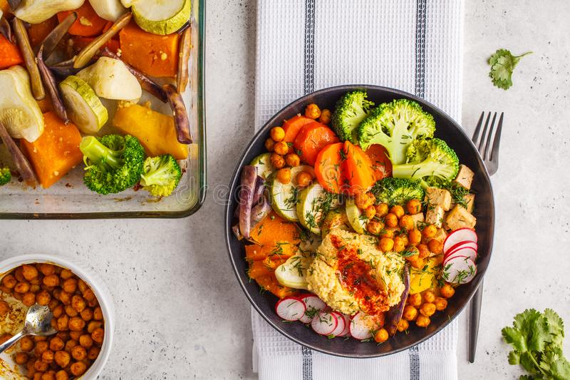 Vegan flat lay, Buddha bowl with baked vegetables, chickpeas, hummus and tofu. stock photos