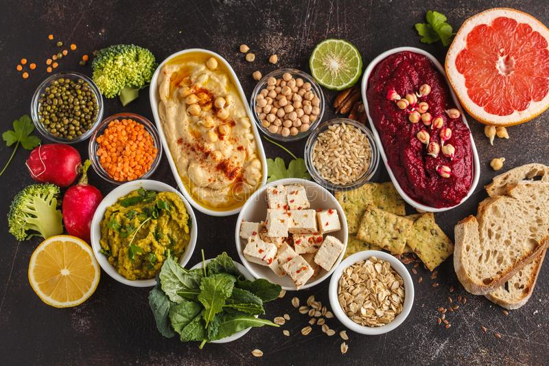 Vegan food background. Vegetarian snacks: hummus, beetroot hummus, green peas dip, vegetables, cereals, tofu. Top view, dark back stock image