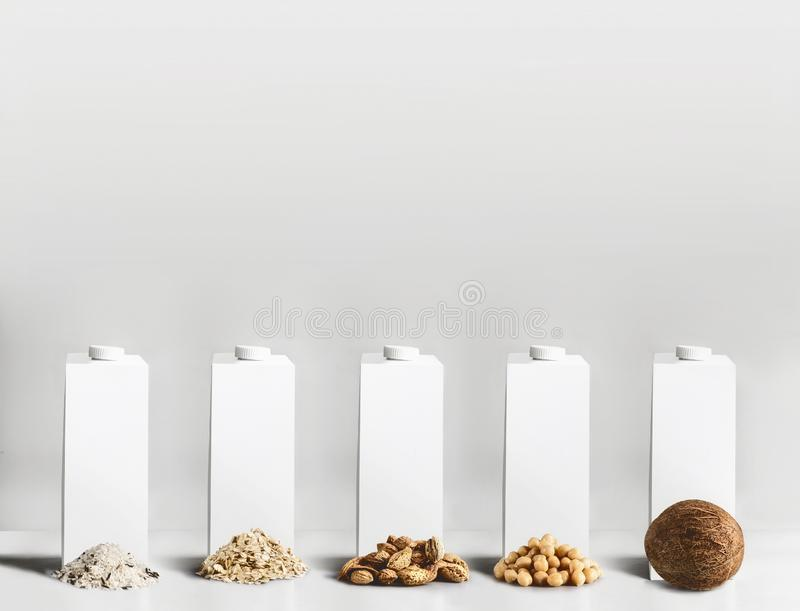 Vegan food concept. Best vegan milk ingredients: rice, oatmeal, almond, soy and coconut with white blank packaging, tetra-pack, royalty free stock photography