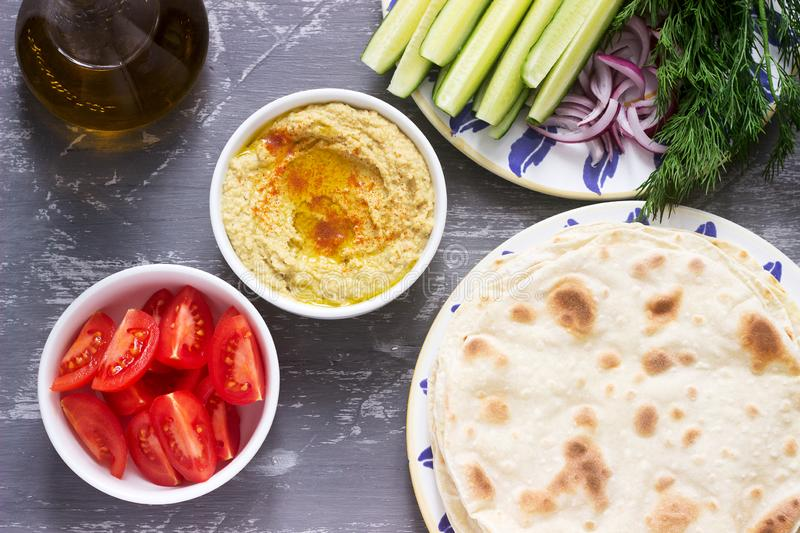 Vegan food, homemade hummus with flatbread, vegetables and olive oil on a concrete background stock photo