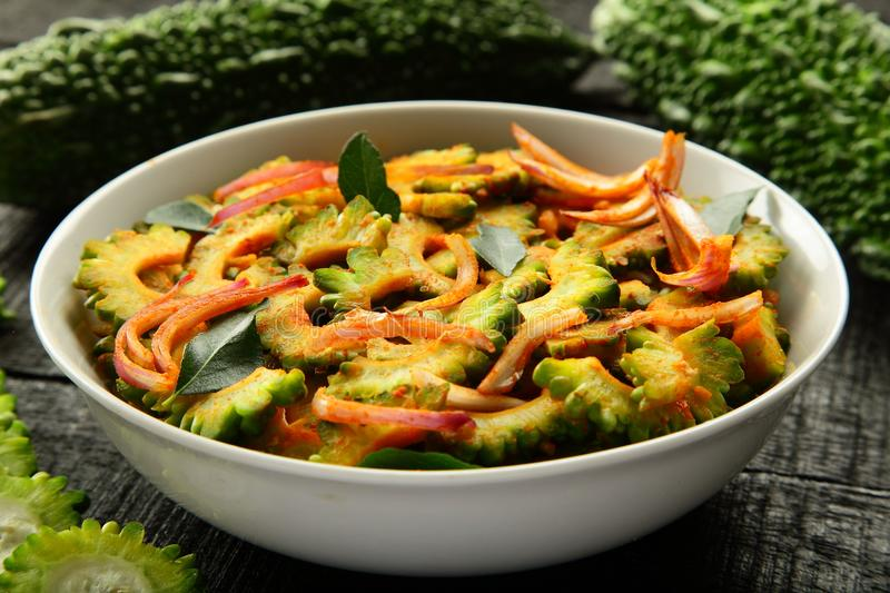 Vegan food Stir fry bitter gourd from Indian cuisine. Homemade spicy fried bitter gourd served in bowl.Indian cuisine.selective focus stock image