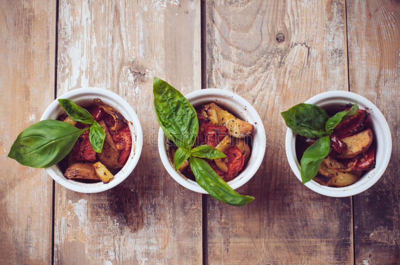 Vegan food: three plates of grilled vegetables. Vegan homemade food: three plates of grilled vegetables, tomatoes, potatoes and peppers with basil on a wooden royalty free stock images
