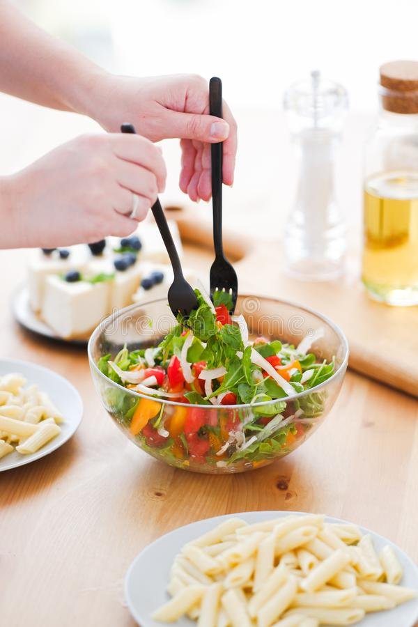 Vegan Food. vegetarian dinner. pasta, vegetables and lactose-free cheesecake. Girl stirs vegetable salad. stock images