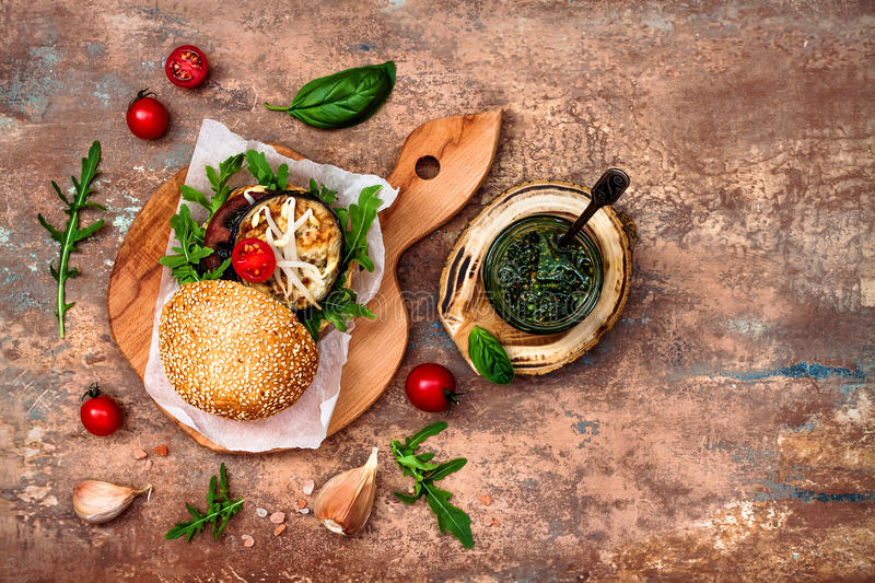Vegan grilled eggplant, arugula, sprouts and pesto burger. Veggie beet and quinoa burger. Top view, overhead, flat lay. Copy space stock images