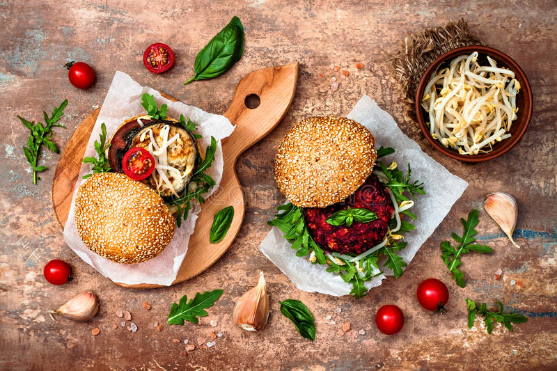 Vegan grilled eggplant, arugula, sprouts and pesto sauce burger. Veggie beet and quinoa burger. Top view, overhead, flat lay. stock photo