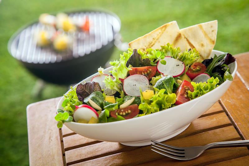 Vegan Healthy fresh leafy green salad on a picnic table. Vegan Healthy fresh leafy green salad in a white ceramic bowl on a wooden picnic table in the sunshine royalty free stock photo