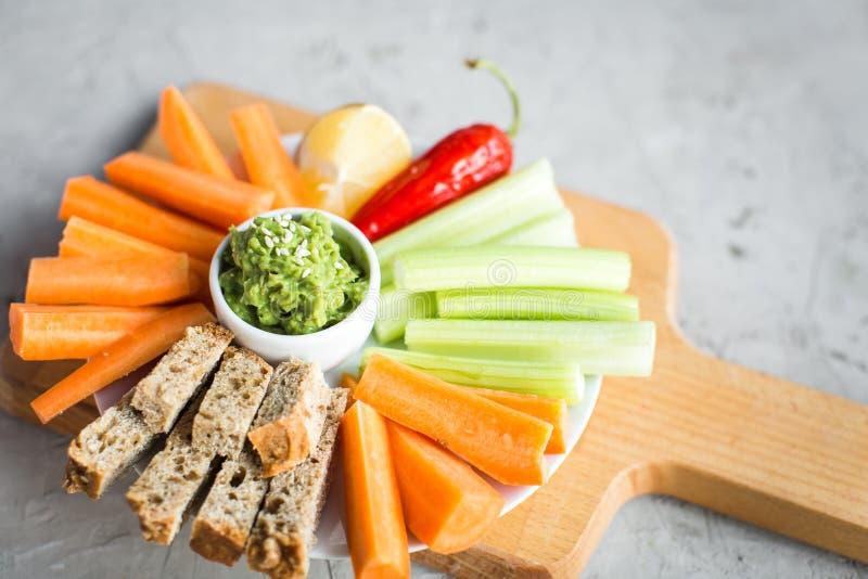 Vegan healthy snacks: guacamole, carrots, celery royalty free stock images