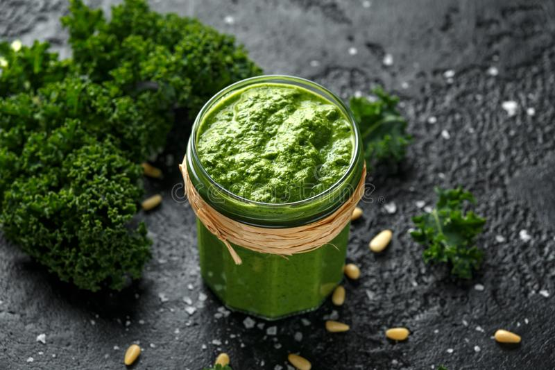 Vegan kale pesto with roasted pine nuts and sea salt flakes royalty free stock images