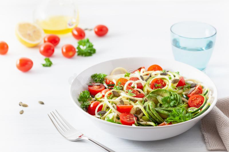Vegan ketogenic spiralized courgette salad with avocado tomato pumpkin seeds stock images