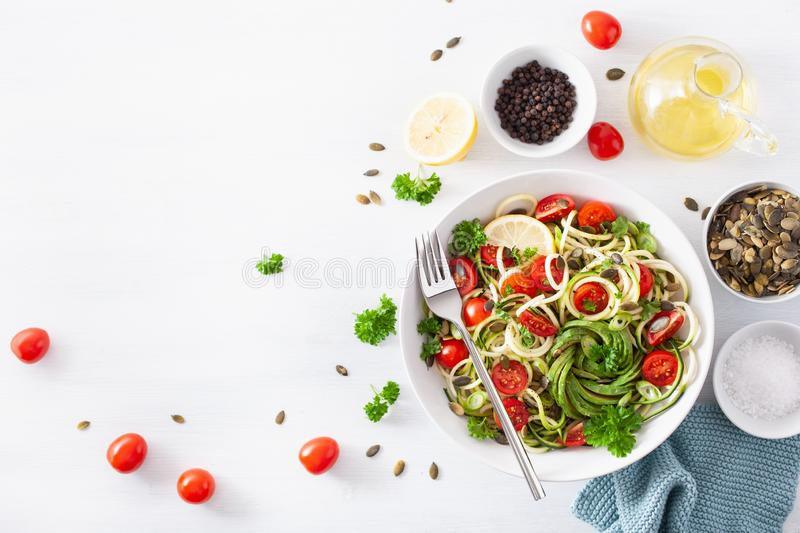 Vegan ketogenic spiralized courgette salad with avocado tomato pumpkin seeds stock photos