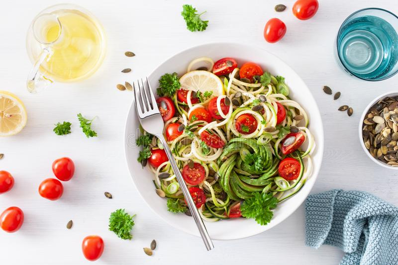Vegan ketogenic spiralized courgette salad with avocado tomato pumpkin seeds royalty free stock photo