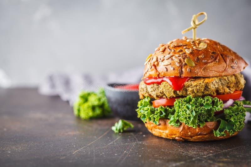 Vegan lentil burger with kale and tomato sauce on a dark background, copy space. Vegan lentil burgers with kale and tomato sauce on a dark background. Plant royalty free stock images