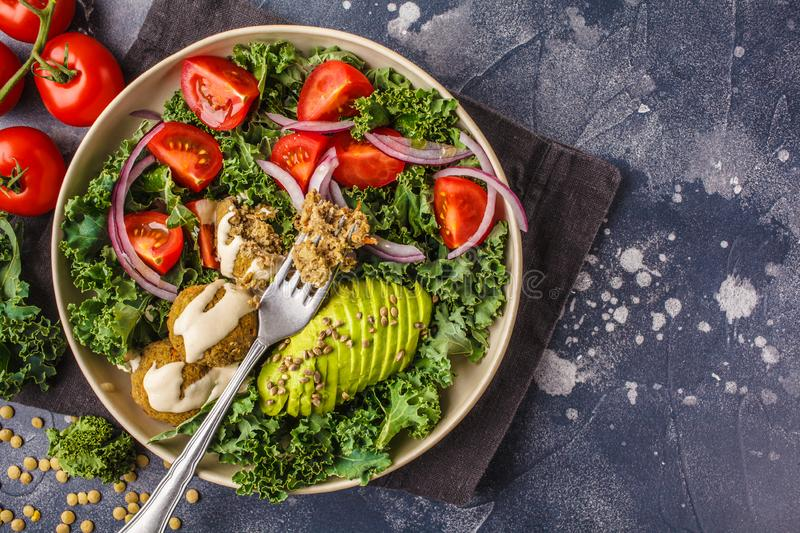 Vegan lentil meatballs salad with kale, avocado, tomato and tahini dressing. royalty free stock images