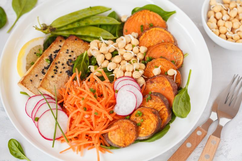 Vegan lunch, salad with vegetables, tofu, baked sweet potato, sp. Routs of chickpeas and green peas. Vegetarian healthy eating concept stock photo