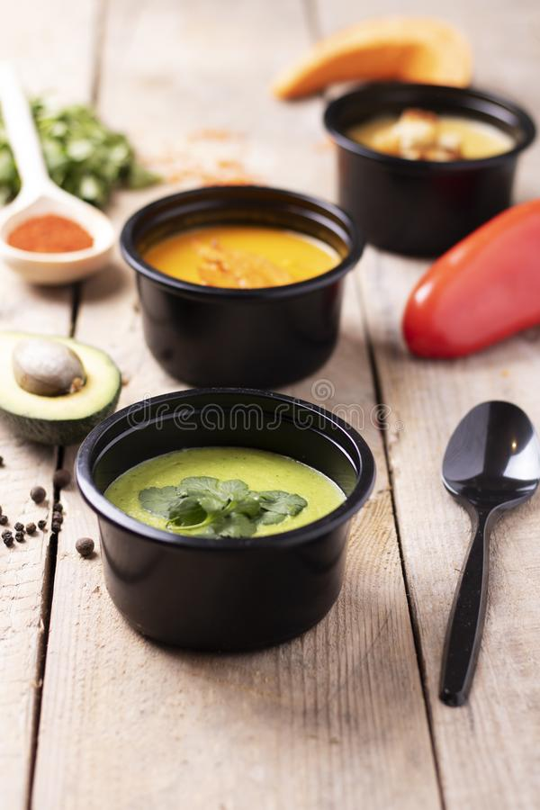 The optimal ratio of proteins, fats and carbohydrates,eco food contain. Vegan lunches in round food boxes, parsley and pepper on wooden table, copy space royalty free stock photography