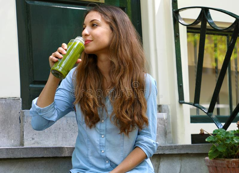 Vegan meal and detox break time concept. Beautiful girl sitting outside her home drinking green juice. Healthy detox vegan diet stock photo