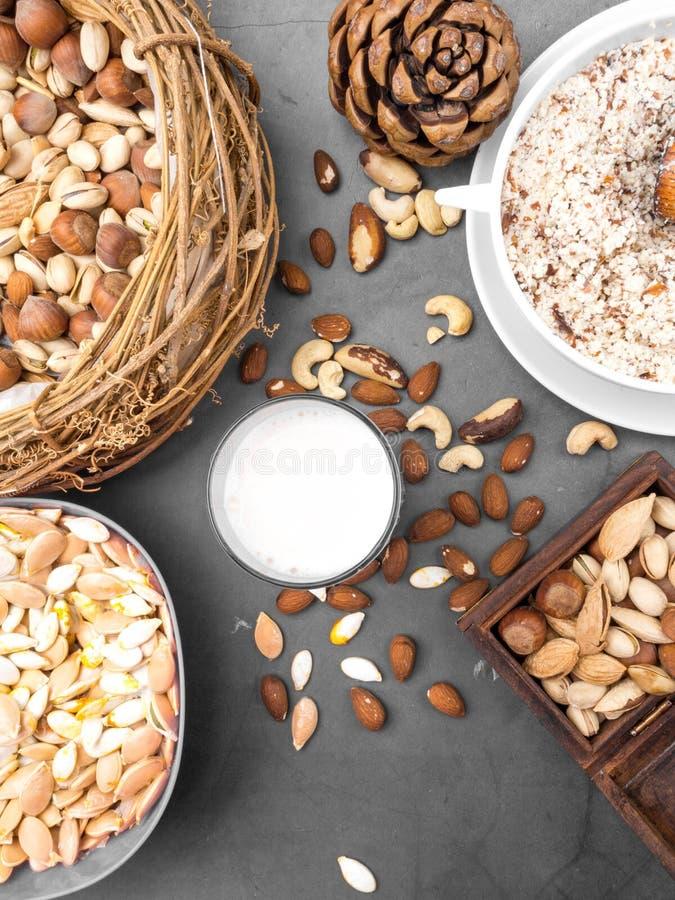 Vegan milk from nuts in glass with various nuts. Organic healthy snack vegan vegetarian stock image