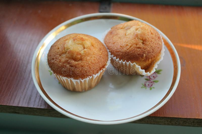 Vegan muffins. Vegetarian two muffins with cholotate inside lay on plate prepare for tea break royalty free stock image