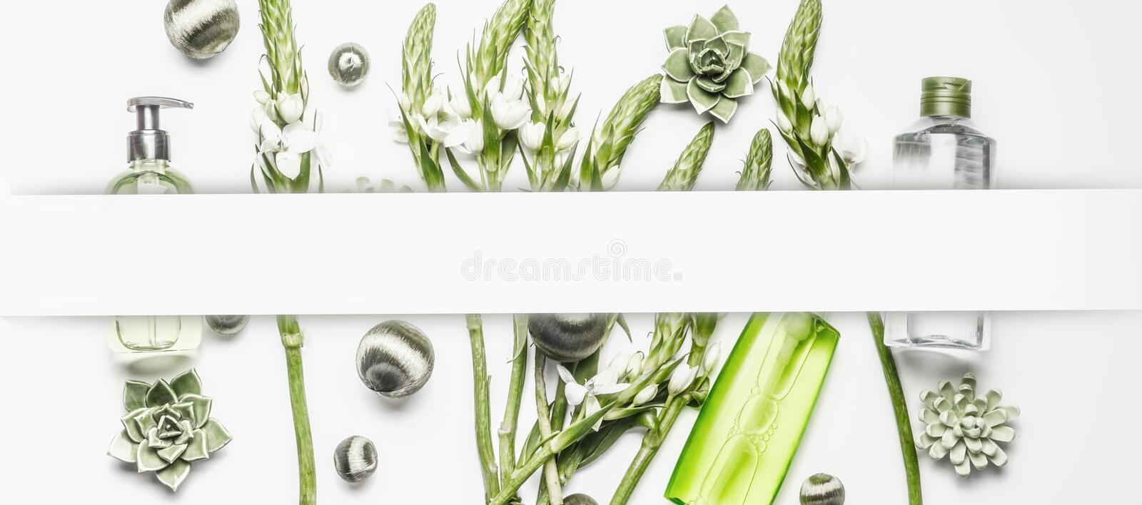 Various cosmetic products with green flowers and plants on white background, frame royalty free stock images