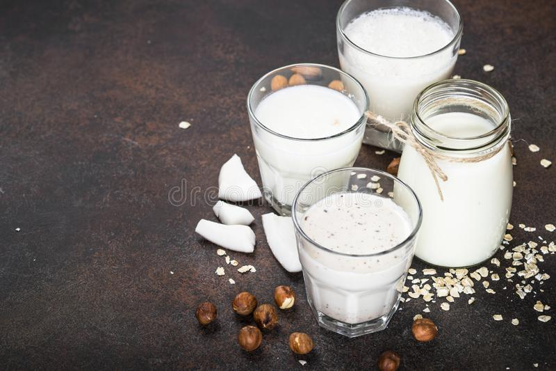 Vegan non dairy alternative milk on dark rusty table. Vegan non dairy alternative milk. Coconut, almond, hazelnut, oat homemade milk on dark rusty table royalty free stock images