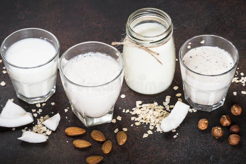 Vegan non dairy alternative milk - nuts and oat. Vegan non dairy alternative milk. Coconut, almond, hazelnut, oat homemade milk on dark table royalty free stock photo