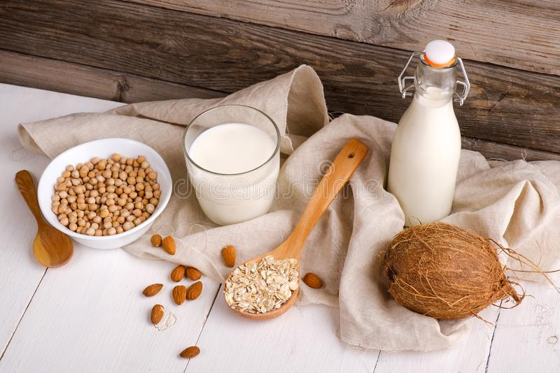 Vegan non dairy milk in bottle and milk alternatives ingredients like a nut, almond, soy, oat on wooden table with kitchen towel. royalty free stock image